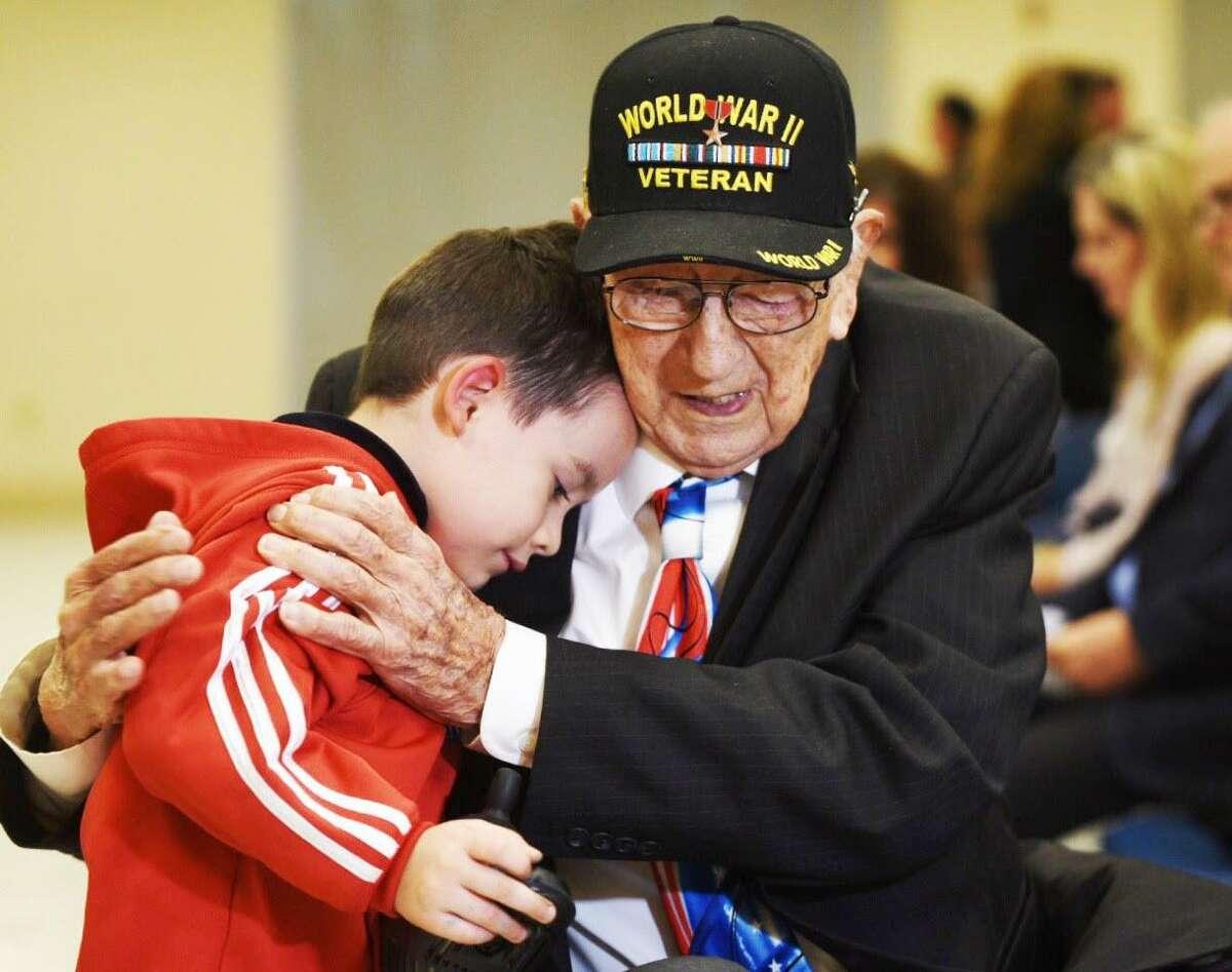 El veterano de la Segunda Guerra Mundial John Valls abraza a su bisnieto John Robert Ortiz, el jueves 2 de mayo de 2019, durante una entrevista en la Biblioteca Pública Joe A. Guerra antes de la ceremonia del Día del Recuerdo por el Holocausto.