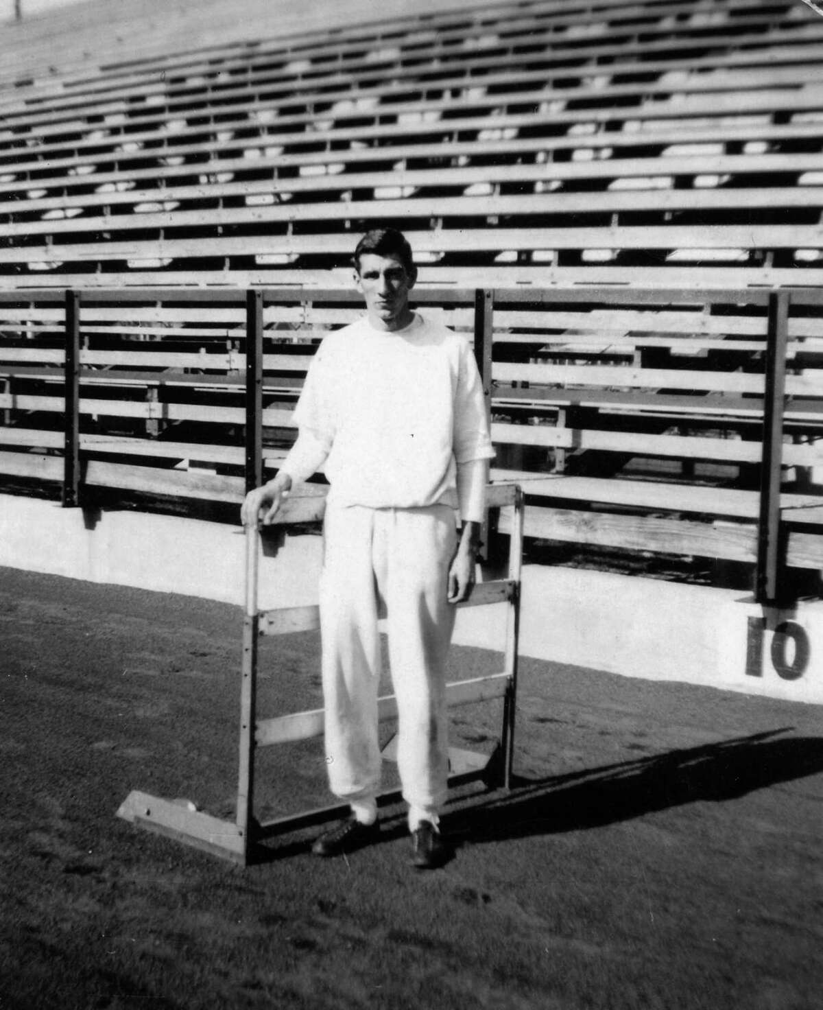 In this undated photo, a young John Valls poses with a track hurdle, an event in which he excelled.