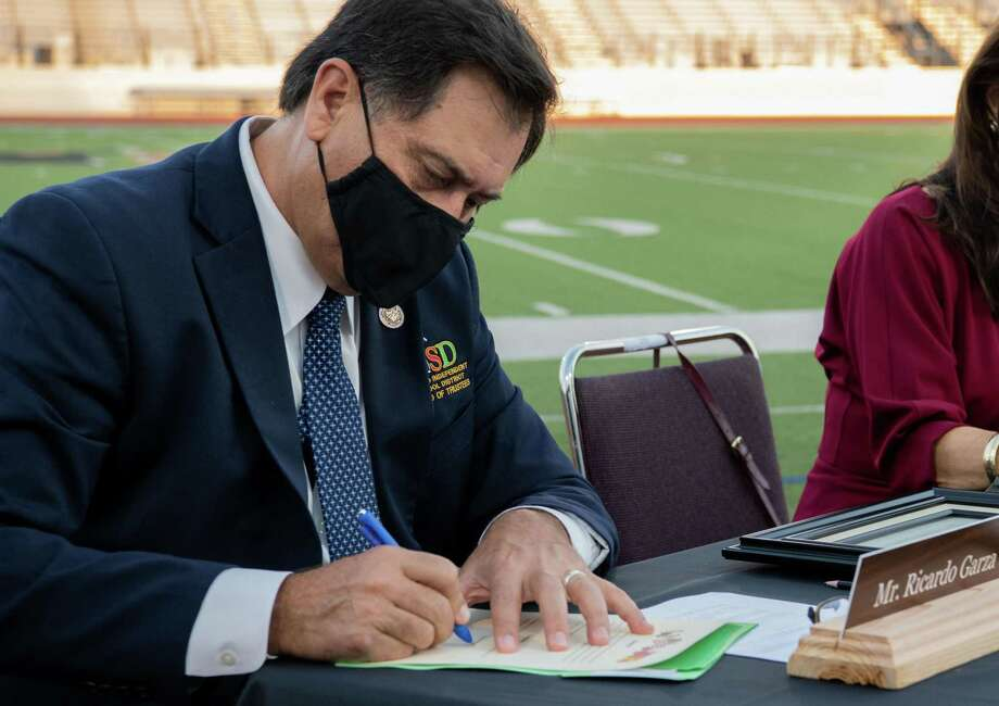 Ricardo 'Rick' Garza signs the Certificate of Election prior to being sworn in at Shirley Field. Photo: Christian Alejandro Ocampo /Laredo Morning Times / Laredo Morning Times