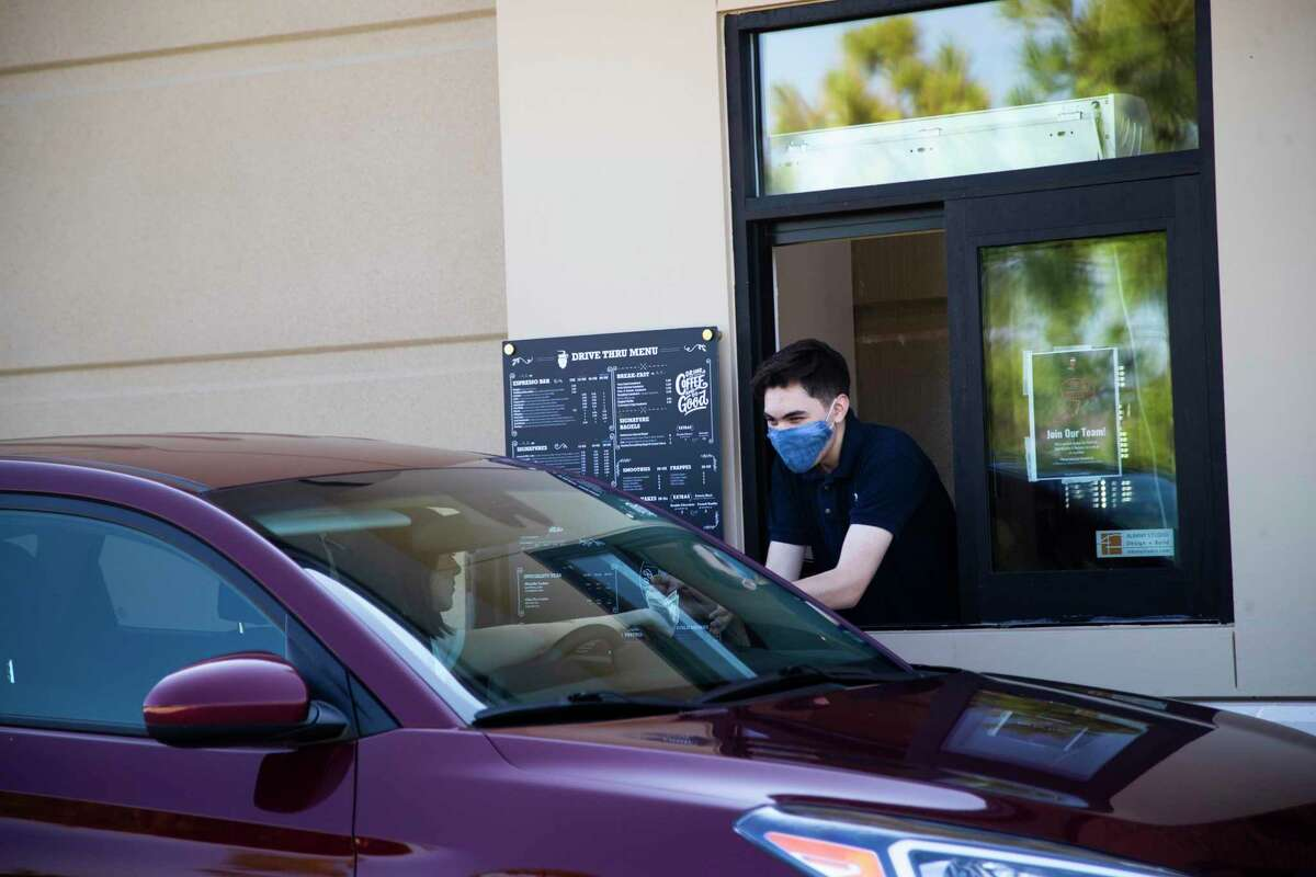 A Barbarossa Coffee staff member Tristan Gutierrez completes a purchase through the drive-thru window of the specialty coffee shop Wednesday, Sept. 16, 2020, in Tomball.