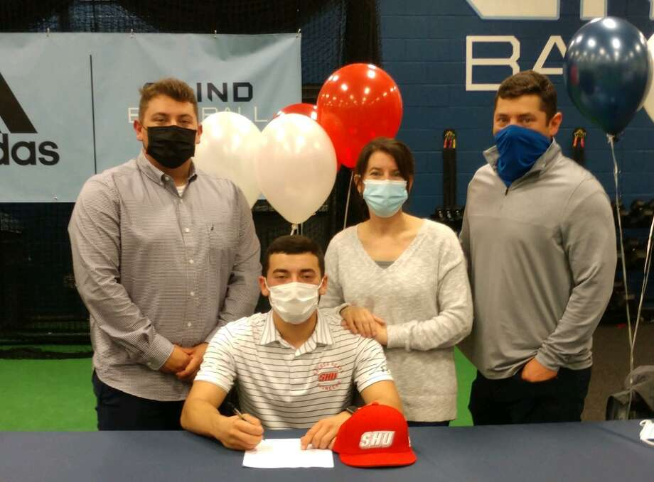 Michael Simonelli signs a letter on intent to play Division 1 baseball at Sacred Heart University. Joining Simonelli, who will pitch for Nick Restaino's Pioneers, are his parents Angelo and Erica and his brother Angelo. Photo: Foran High Athletics / Contributed Photo / Milford Mirror