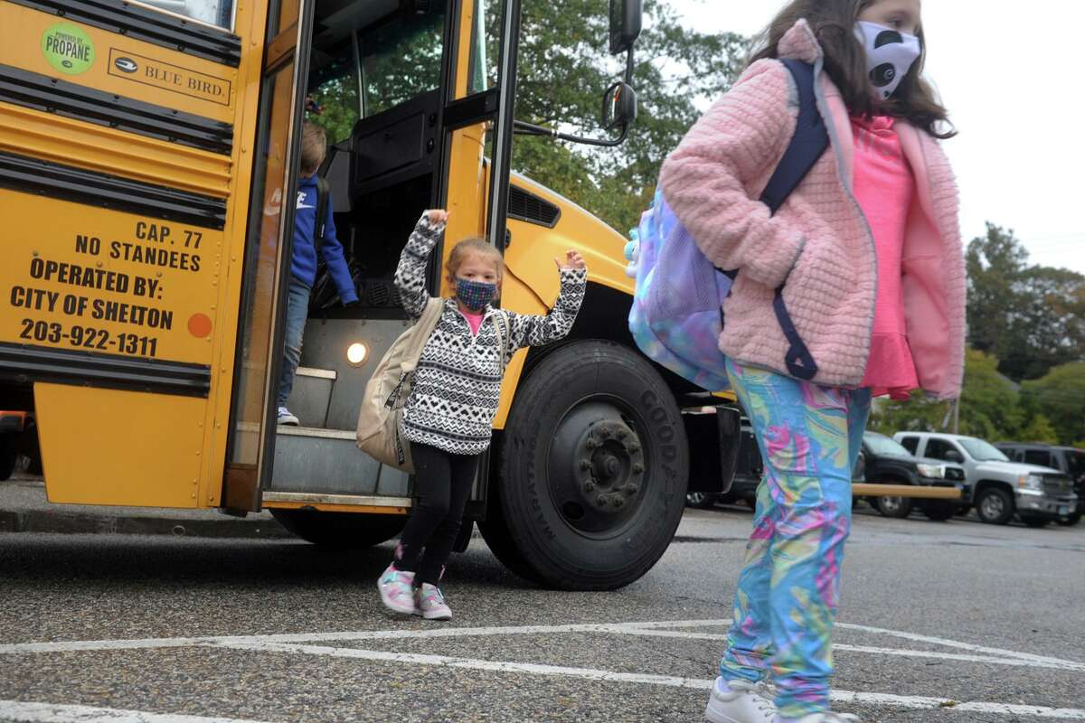 Students disembark from a school bus as the arrive at Sunnyside Elementary School, in Shelton, Conn. Oct. 13, 2020.