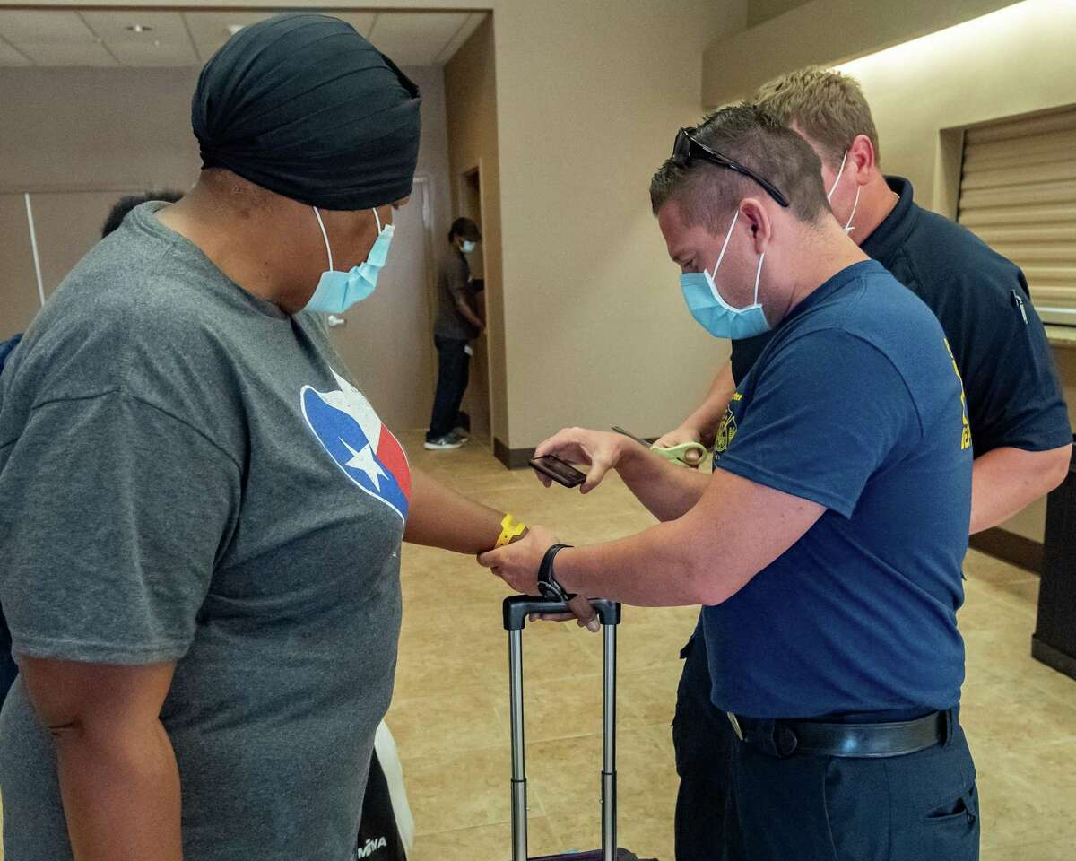 Firefighter William Merkelz scans the wristband worn by Janice Howard to complete her evacuation process. The first Hurricane Laura evacuees returned to the Port Arthur Civic Center on Monday afternoon. Photo made on August 31, 2020. Fran Ruchalski/The Enterprise