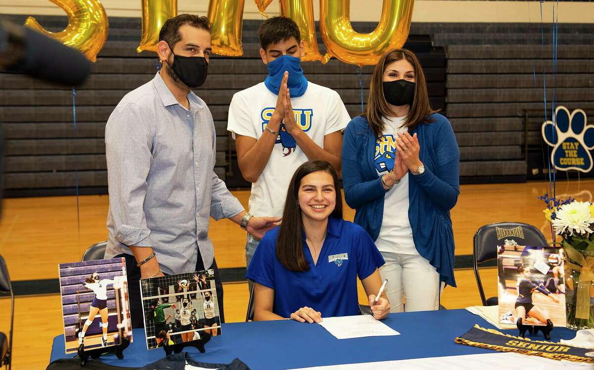 Mick Cruz, Nicholas Cruz and Terry Cruz celebrate as Leah Cruz signs her National Letter of Intent to play volleyball at St. Mary's University on Wednesday, Nov. 11 at Alexander High School.