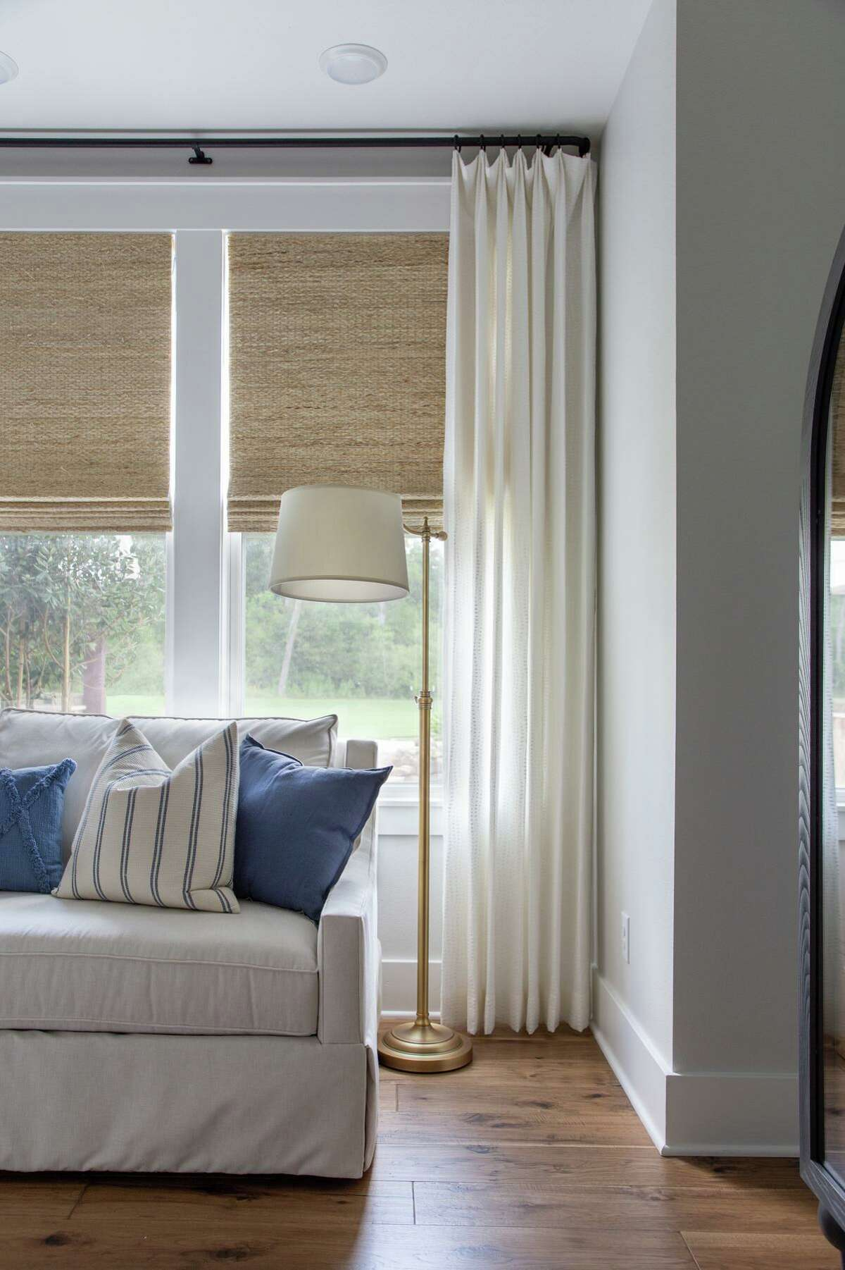 Moore House Interiors layered blackout-lined seagrass window shades with linen draperies in the primary bedroom.