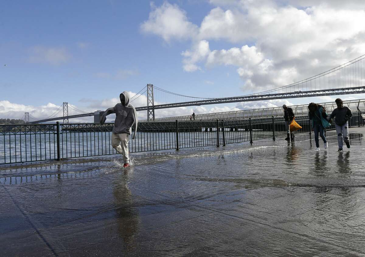 Pedestrians walk through water from a king tide that flooded onto the Embarcadero in San Francisco, Wednesday, Jan. 11, 2017.