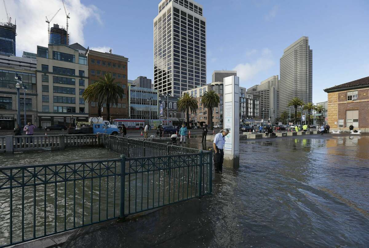 Rudy Sales, center, stands in water from a king tide that flooded onto the Embarcadero in San Francisco, Wednesday, Jan. 11, 2017.
