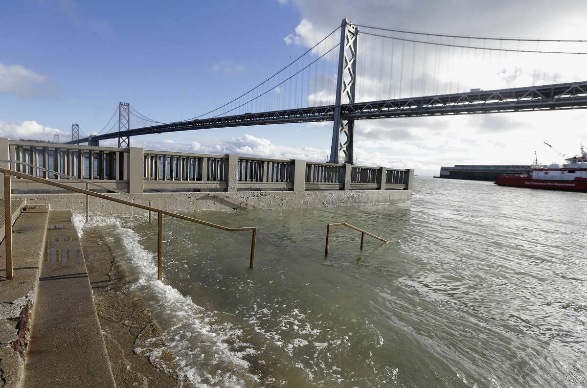In this Jan. 11, 2017, file photo, water from a king tide floods a staircase along the Embarcadero in San Francisco.