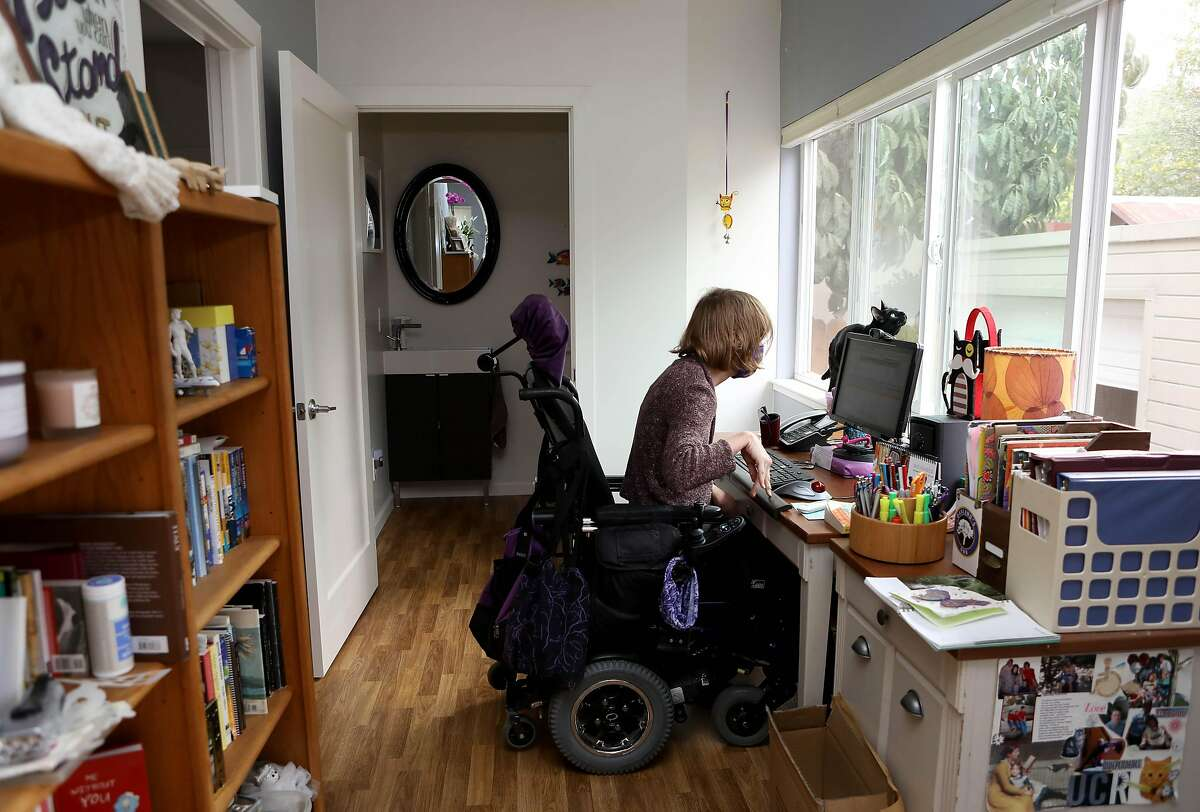 Melissa Cooper works in her home office in Oakland Wednesday. She uses a power wheelchair to get around.
