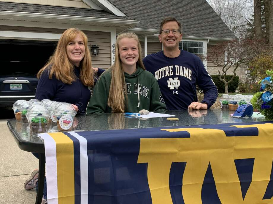 Midland High's Natalie Hoefer poses with her mother Nancy and father Kurt as part of a ceremony outside the Hoefer home Wednesday, during which Hoefer signed a National Letter of Intent to join the Notre Dame rowing team. Photo: Fred Kelly/fred.kelly@mdn.net