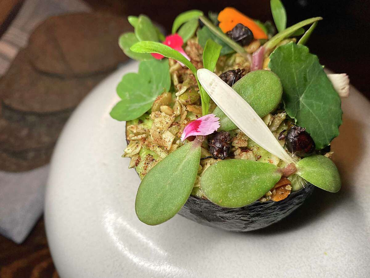 Guacamole with Oaxacan ants called chicatanas, roasted grasshoppers, cilantro, purslane, nasturtium flowers and a side of blue corn tostadas is part of the multicourse menu at Kumo.