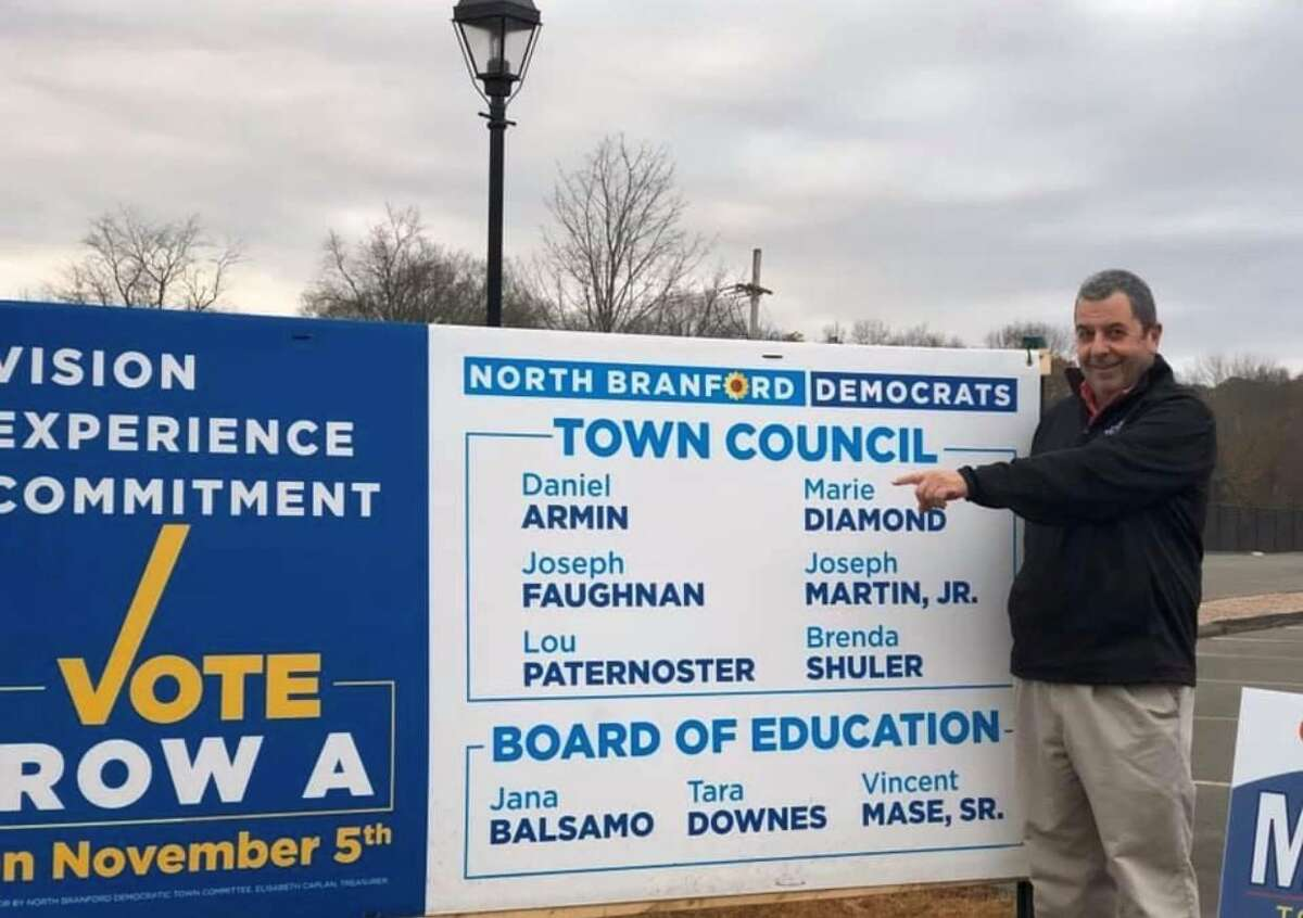 """The late Lewis """"Lou"""" Paternoster in Nov. 2019 won a seat on the Town Council in North Branford, Conn. He is pictured next to a campaign sign. On Paternoster's team, everyone got playing time. """"He would look at his team and he would figure out what each person could bring to that team,"""" Betty Jo Paternoster said. """"Every kid that was on the team played in the game, and they played in all the games, and they all played ... their best move... That was an amazing thing that I saw him do over and over and over again."""" As a referee, Lou Paternoster wouldn't just call fouls - he would coach players through their mistakes, said Donna Ricci, who said she served on a basketball board with Paternoster. """"He always wanted everything to be a learning experience - and a fun experience,"""" she said. 'The Mayor' Unfailingly, people who remembered Paternoster noted his sense of humor. """"He was hilarious,"""" Ricci said. When Paternoster umpired a baseball game, there was no shortage of laughter between innings, according to Mascari, who is president of the North Branford Little League board. """"He's supposed to be umpiring, and he's just chatting ... with everybody,"""" he said. """"He'd be holding court back there."""""""