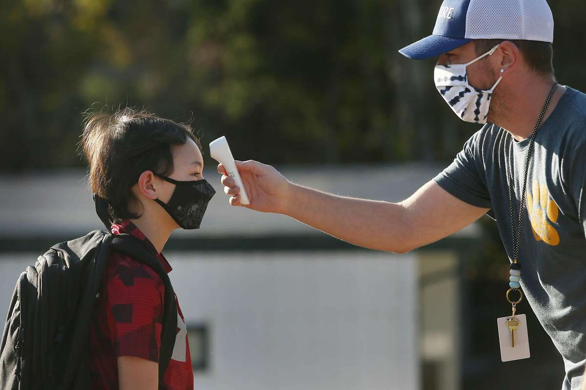 Nathan Grebil takes the temperature of fourth-grader Andrew, 9, at Bel Aire Elementary School in Tiburon in October.