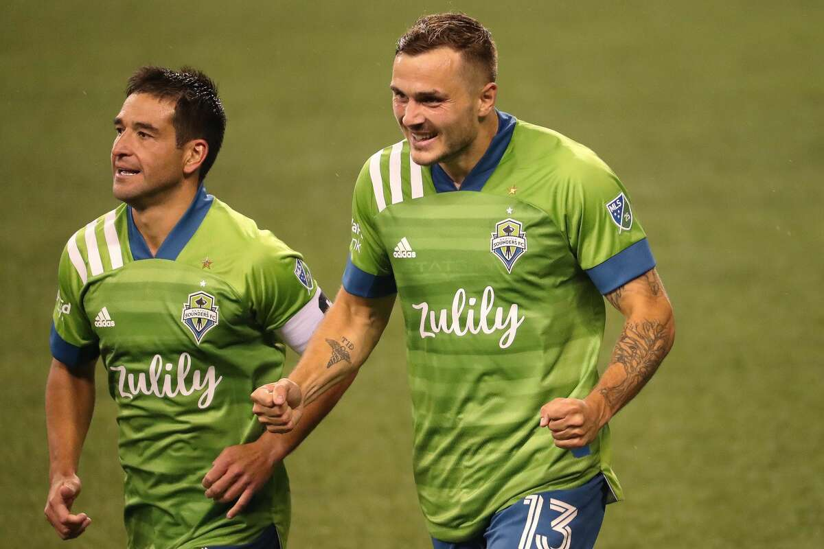 SEATTLE, WASHINGTON - AUGUST 30: Jordan Morris #13 celebrates alongside Nicolas Lodeiro #10 of Seattle Sounders after scoring his second goal of the night to take a 3-0 lead against Los Angeles FC in the second half at CenturyLink Field on August 30, 2020 in Seattle, Washington. (Photo by Abbie Parr/Getty Images)
