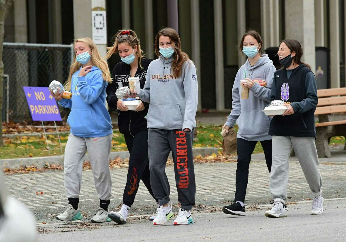 Students walks to Indian Quad dormitory with their lunch at University at Albany on Thursday, Nov. 12, 2020 in Albany, N.Y. Students are no longer allowed to dine inside the foodcourt area due to rises in COVID-19 cases.