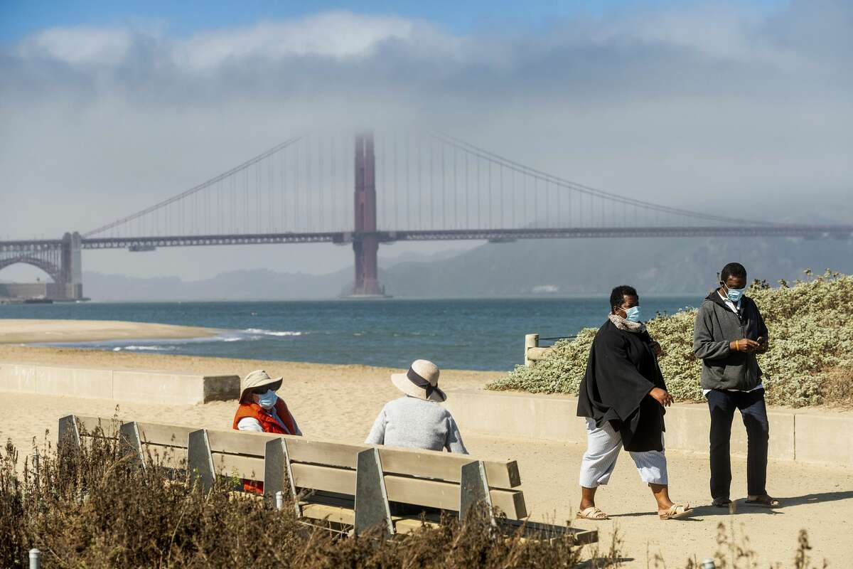 In this Oct. 22, 2020, file photo, with the Golden Gate Bridge in the background, people wear face masks while strolling at Crissy Field East Beach in San Francisco. San Francisco will temporarily halt the reopening of additional activities and businesses planned for next week week because of an increase in coronavirus case rates and hospitalizations, the city's mayor and health director said Friday, Oct. 30, 2020.