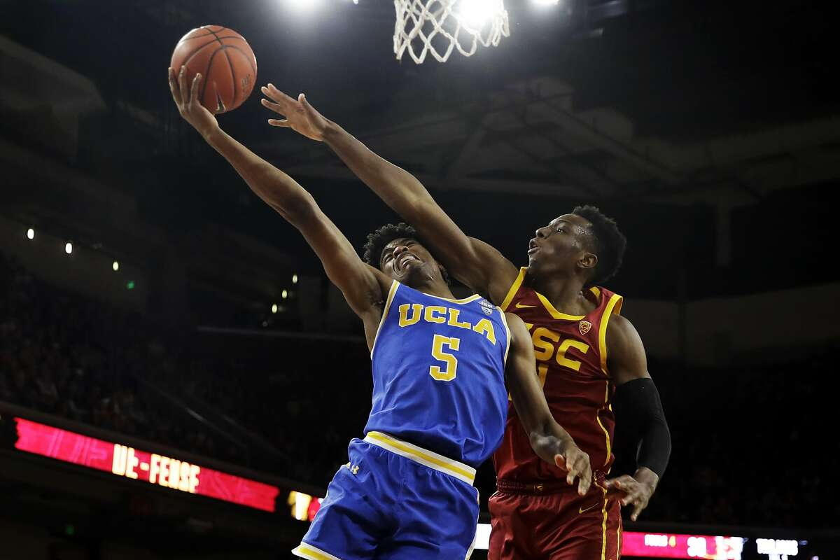 In this Saturday, March 7, 2020, file photo, UCLA guard Chris Smith (5) drives to the basket as Southern California forward Onyeka Okongwu defends during the second half of an NCAA college basketball game, in Los Angeles. After flirting with the NBA draft, Smith has returned to UCLA for the 2020-21 season.