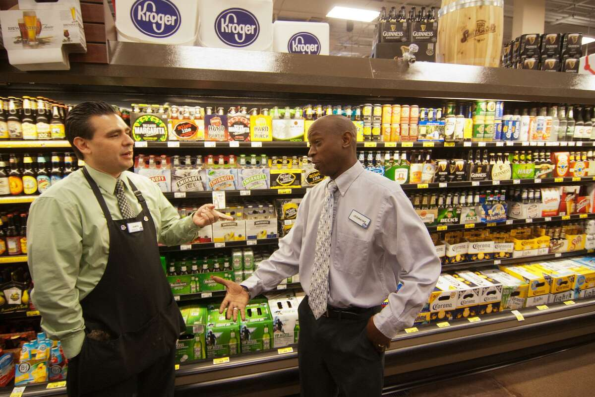 Wine consultant James DeLeon, and wine steward Jermaine Brown talk wines in front of the beer display at the Montrose Kroger store.