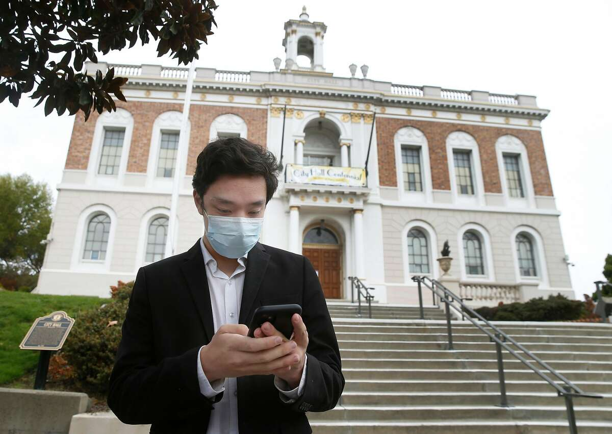 City Council member-elect James Coleman checks for messages on his phone at City Hall in South San Francisco.