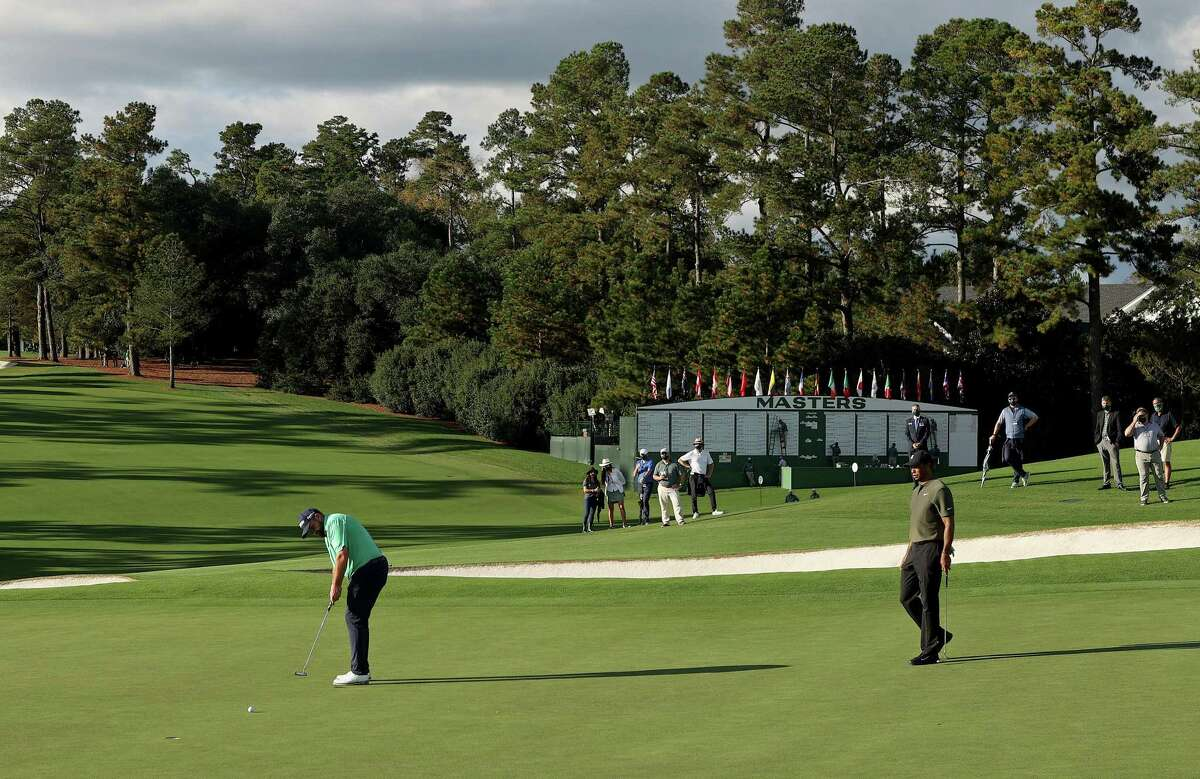 AUGUSTA, GEORGIA - NOVEMBER 12: Shane Lowry of Ireland putts on the ninth green as Tiger Woods of the United States looks on during the first round of the Masters at Augusta National Golf Club on November 12, 2020 in Augusta, Georgia.