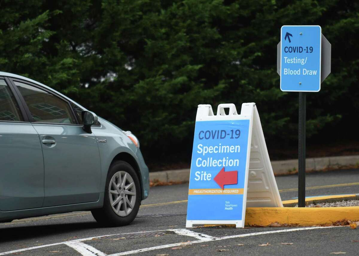 A car drives to the COVID-19 specimen collection site at Greenwich Hospital in Greenwich, Conn. Thursday, Nov. 12, 2020.