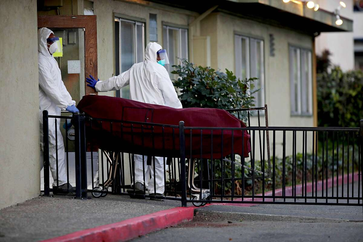 """Men donning hazmat suits bring a body out of Gateway Care and Rehabilitation, located at 26660 Patrick Ave., on Wednesday, April 8, 2020, in Hayward, Calif. Six residents at the skilled nursing home in Hayward have died after being infected by the coronavirus in an outbreak at the facility that has infected 29 other residents and 24 staff members. Alameda County public health spokeswoman Neetu Balram confirmed the outbreak Wednesday afternoon.Officials are also monitoring an outbreak at East Bay Post-Acute Rehab in Castro Valley where seven people, including four staffers, have tested positive. Balram cautioned the number of infected persons at each facility could be updates and should be considered a """"point-in-time"""" count. Health officials are tracing suspected and confirmed cases of COVID-19 at long-term care facilities throughout the county, Balram said."""