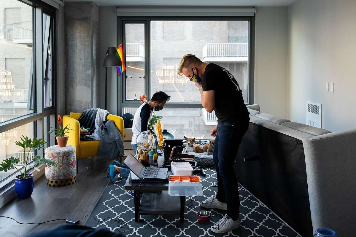 """Reagan Rockzsfforde (left) and Christopher Beale unpack at their new home in San Francisco, where the future is """"up to the people,"""" Beale said. """"The slate has been wiped clean in a way."""""""
