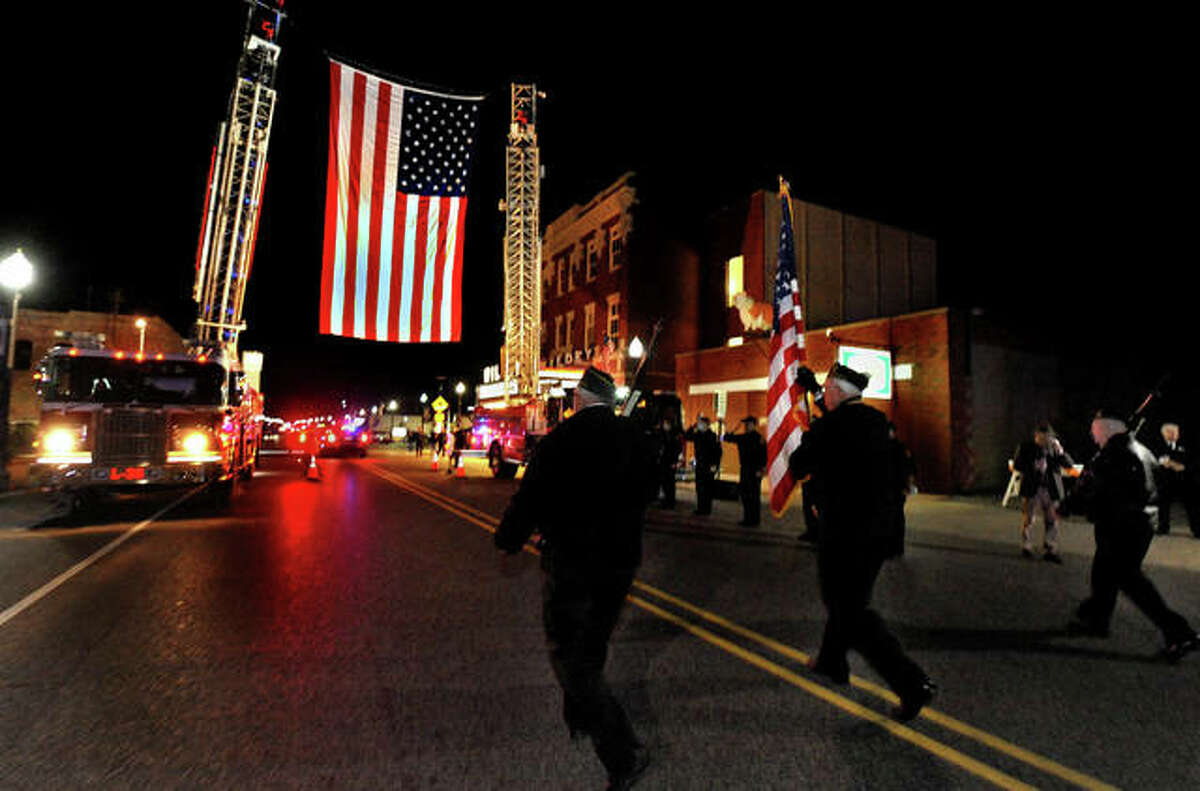 Veterans march toward a large flag suspended by the Edwardsville Fire Department during a Veteran's Day parade Wednesday evening on Main Street.