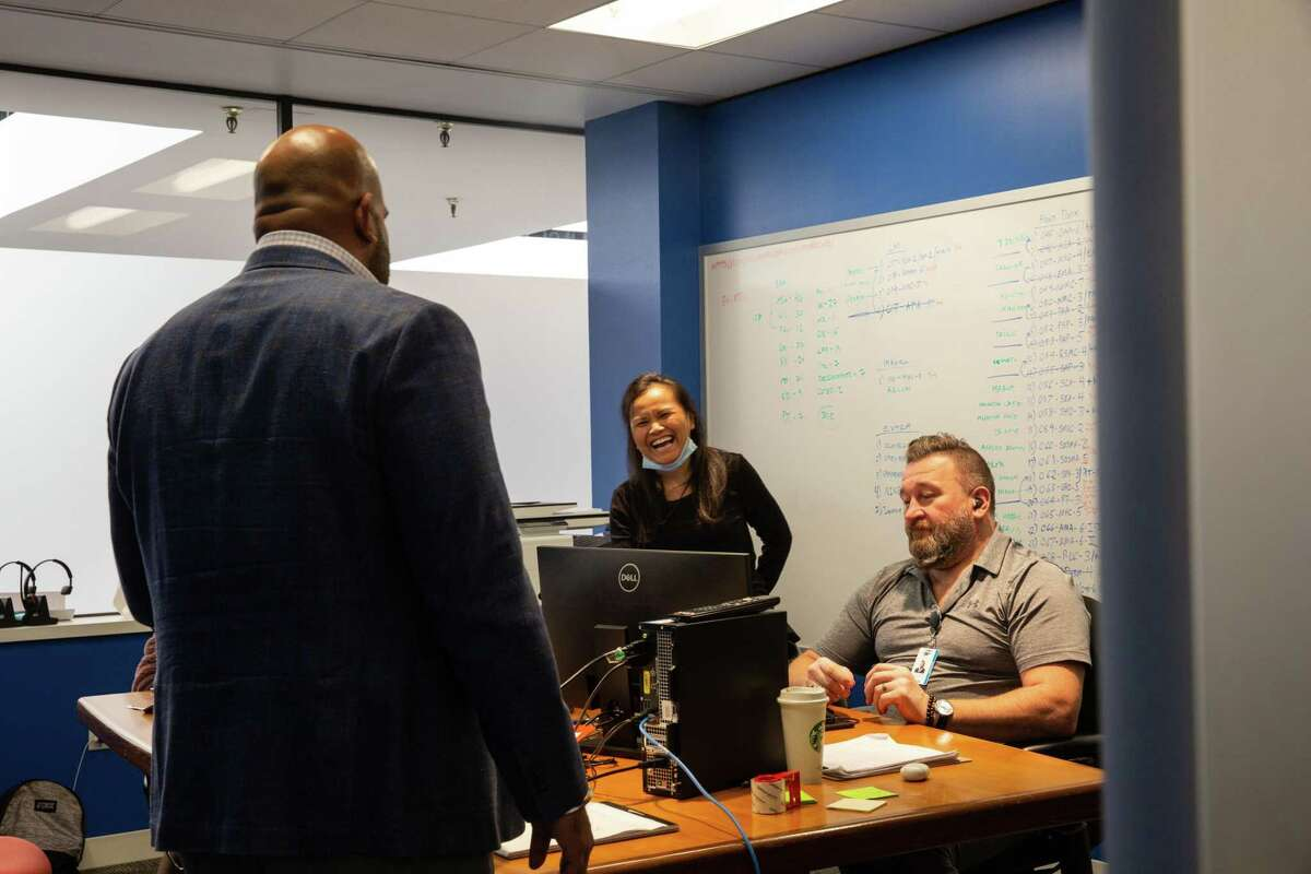 Virtual command center lead Souban Houn laughs as she chats with Sonny Hyare at the office on Nov. 6, 2020.