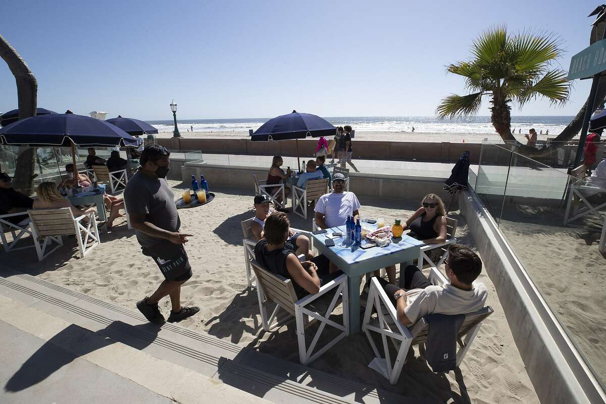 Diners sit at outside tables at the Beach House Grill in San Diego, May 21, 2020.