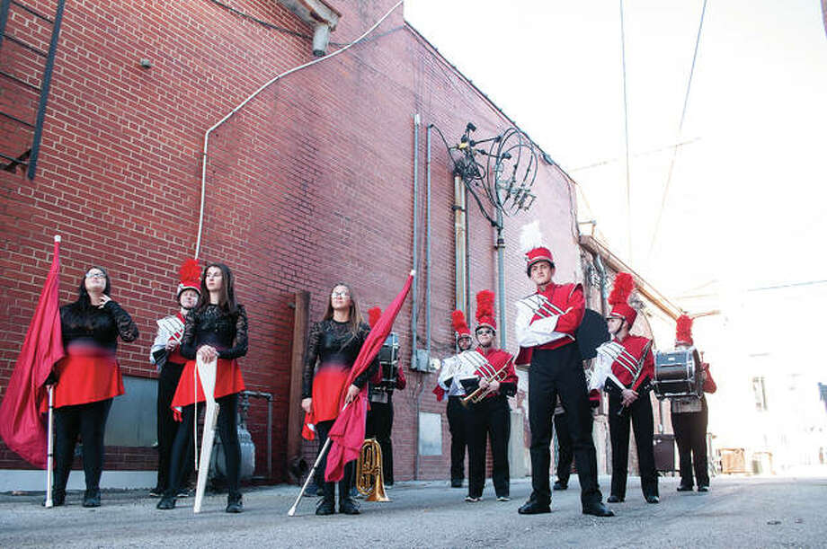 Photographer Karen Anderson directs the Jacksonville High School marching band on Thursday while setting up for senior photos. The photo shoot took place in an alley off Main Street.