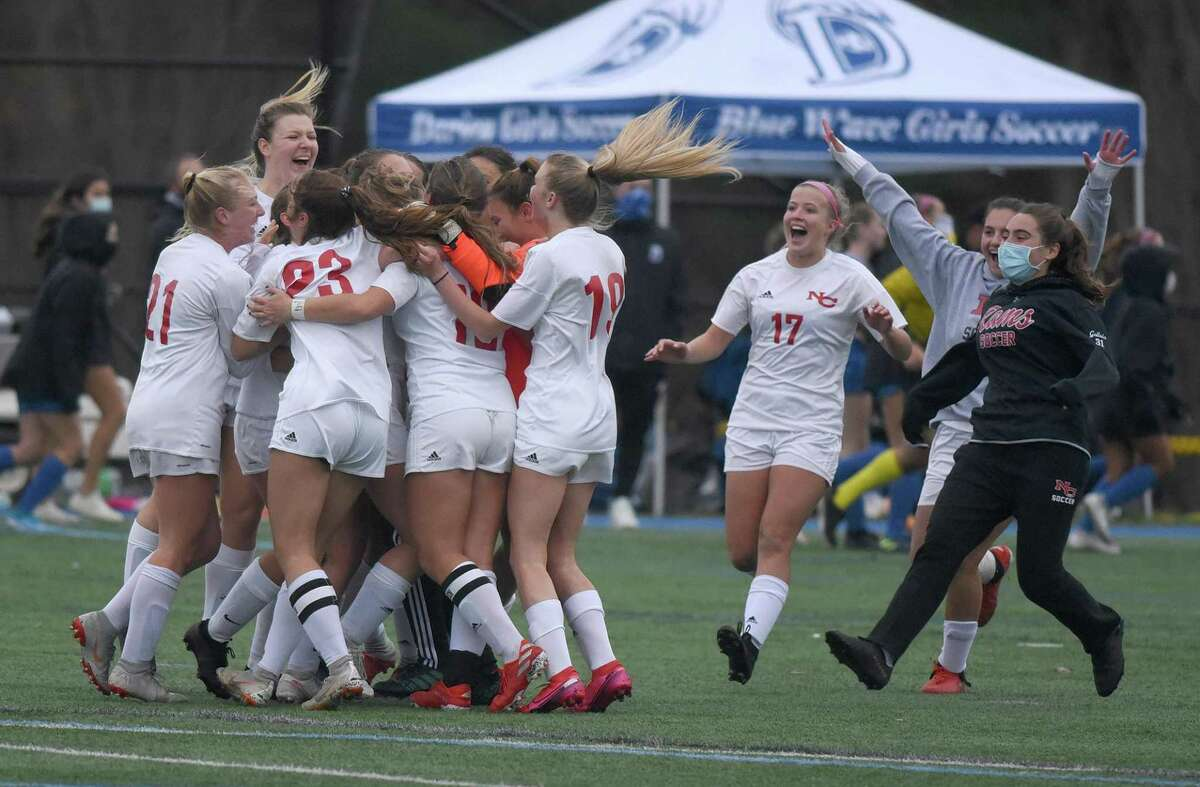 The New Canaan girls soccer team celebrates after defeating rival Darien 2-1 in the FCIAC West Region final in Darien on Thursday, Nov. 12, 2020.