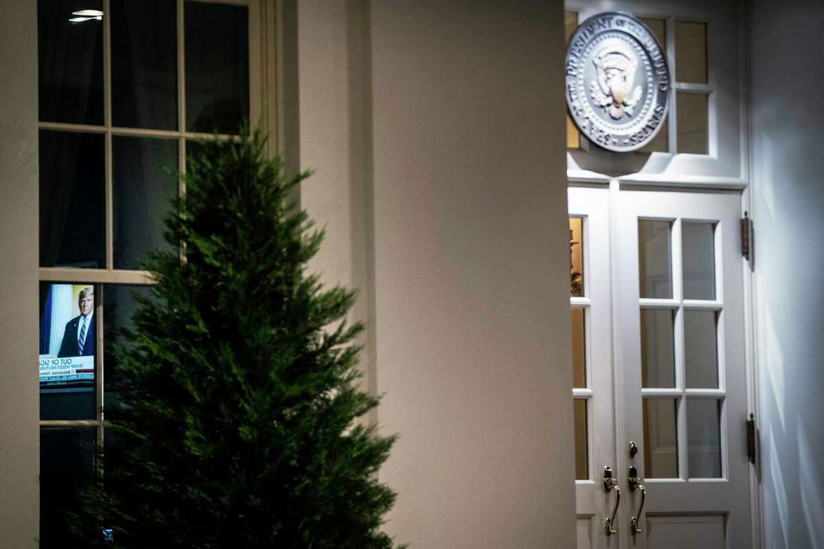 A television is seen through a window near the entrance to the West Wing of the White House on Tuesday night. President Trump's sole public event this week was a wreath-laying at a Veterans Day ceremony.