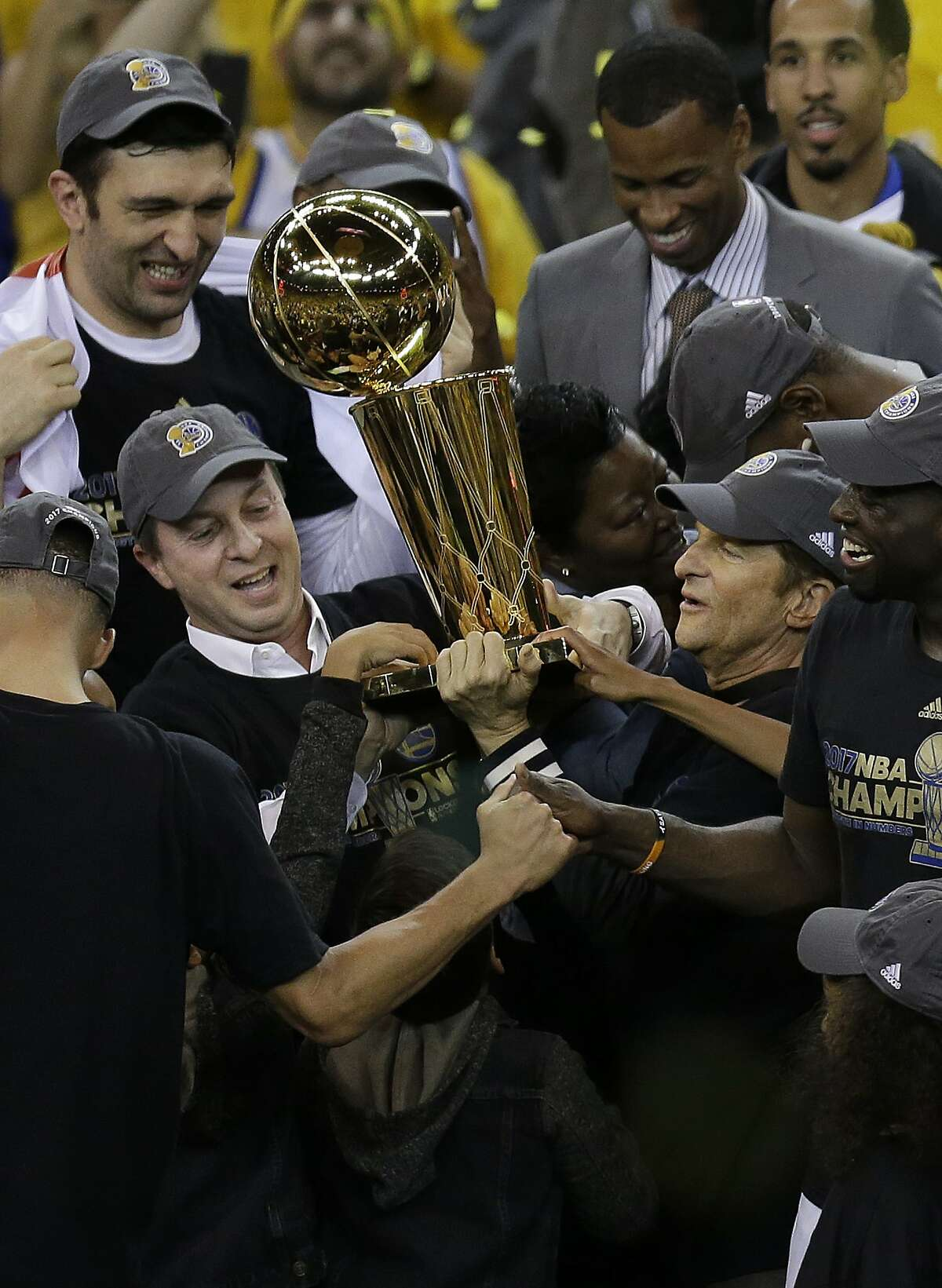 Golden State Warriors owners Joe Lacob, center left, and Peter Guber, center right, hold up the Larry O'Brien NBA Championship Trophy after Game 5 of basketball's NBA Finals between the Warriors and the Cleveland Cavaliers in Oakland, Calif., Monday, June 12, 2017. The Warriors won 129-120 to win the NBA championship.. (AP Photo/Ben Margot)