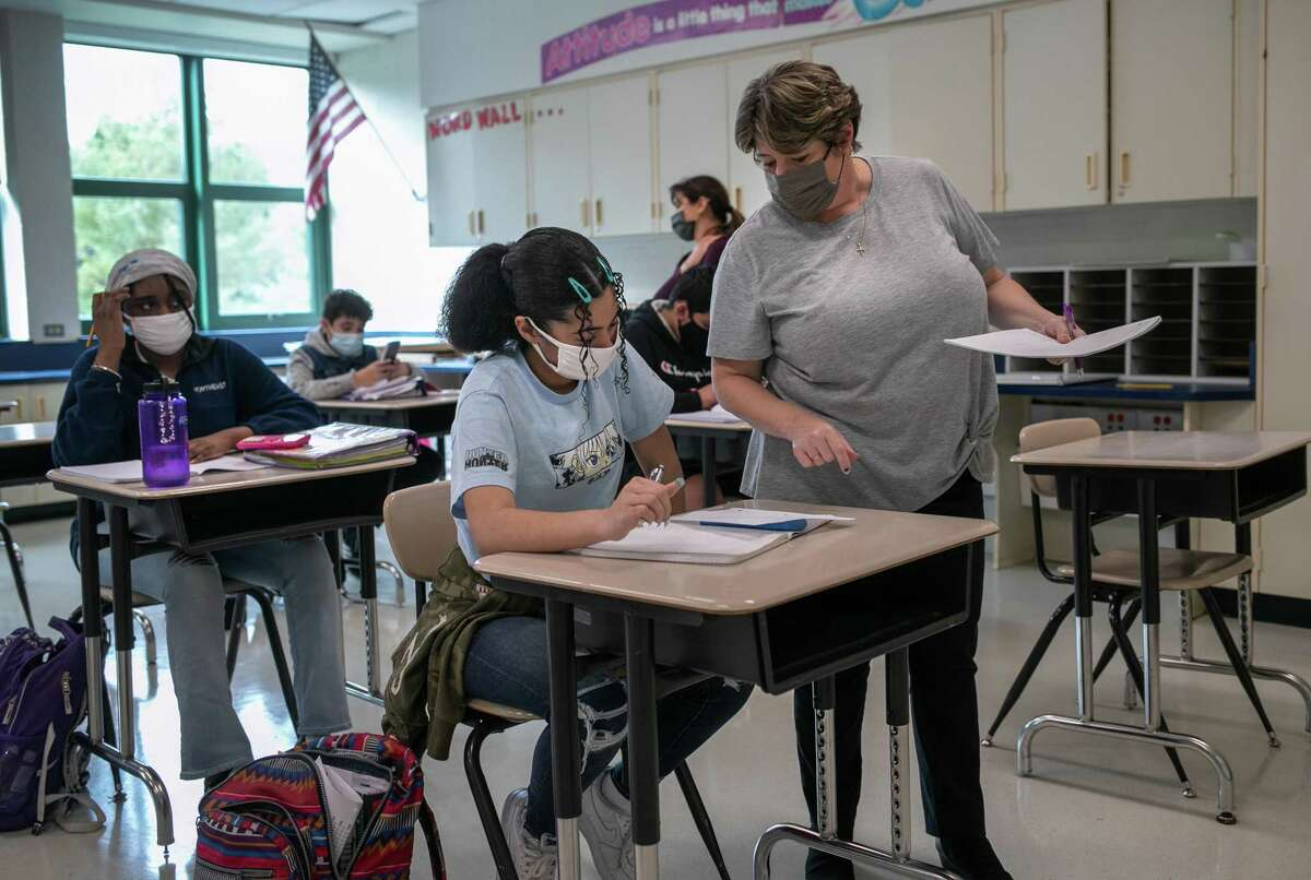 Eighth-grade math teacher Leeann Heller helps a student at Scofield Magnet Middle School on Oct. 27 in Stamford.