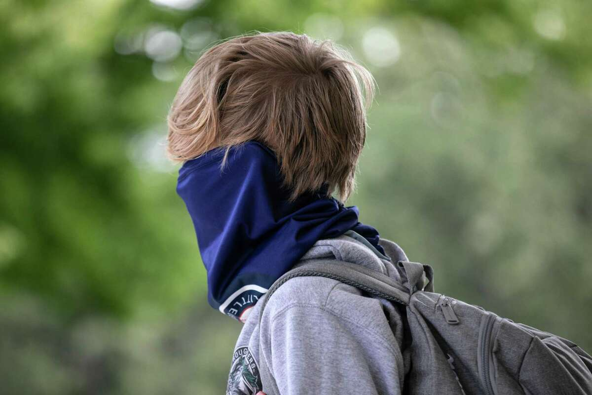 A student, his face covered, waits for the doors to open after drop-off at Rippowam Middle School on September 14, 2020 in Stamford, Connecticut.