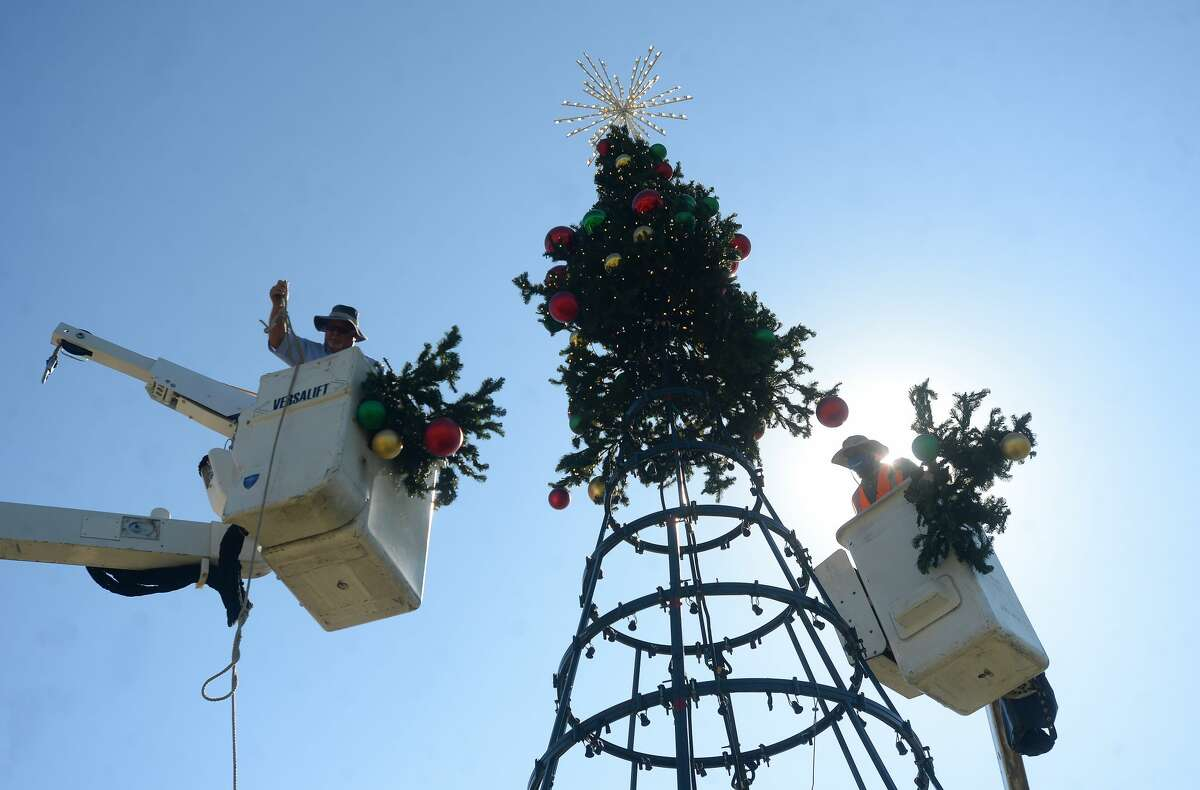 Terry Burd (left) and Andrea Nolbert affix the decorated branches to the top of the tree as workers with the City of Beaumont worked throughout the day Thursday to erect the Christmas tree outside the Event Centre. Photo taken Thursday, November 12, 2020 Kim Brent/The Enterprise