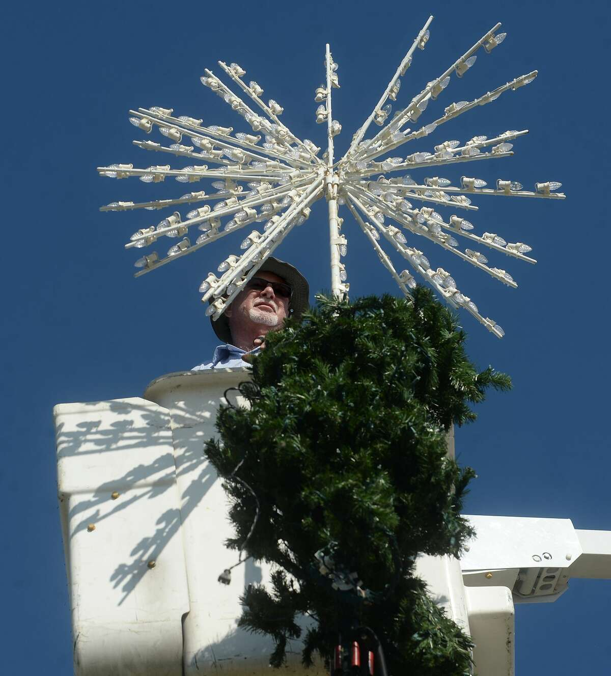 Terry Burd places the 3-dimensional star atop the tree as he and workers with the City of Beaumont worked throughout the day Thursday to erect the Christmas tree outside the Event Centre. Photo taken Thursday, November 12, 2020 Kim Brent/The Enterprise