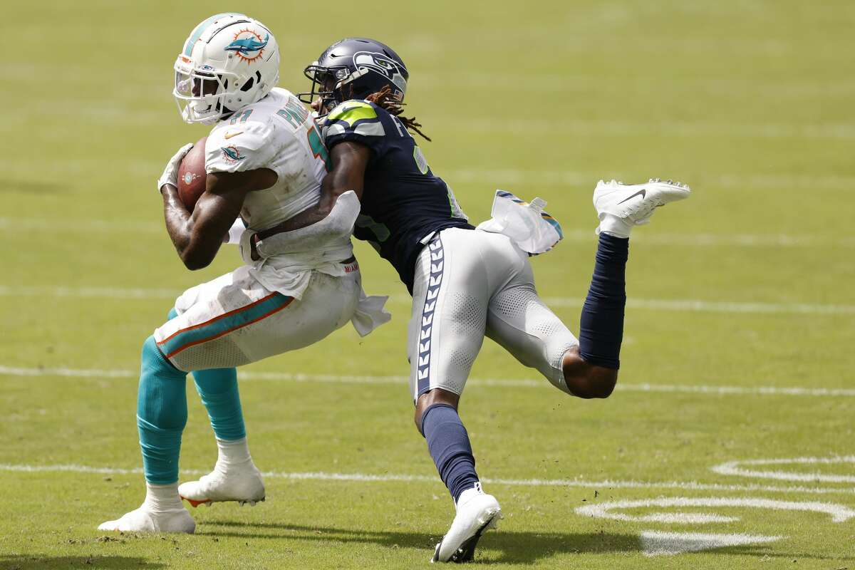 MIAMI GARDENS, FLORIDA - OCTOBER 04: DeVante Parker #11 of the Miami Dolphins is tackled by Tre Flowers #21 of the Seattle Seahawks during the second half at Hard Rock Stadium on October 04, 2020 in Miami Gardens, Florida. (Photo by Michael Reaves/Getty Images)