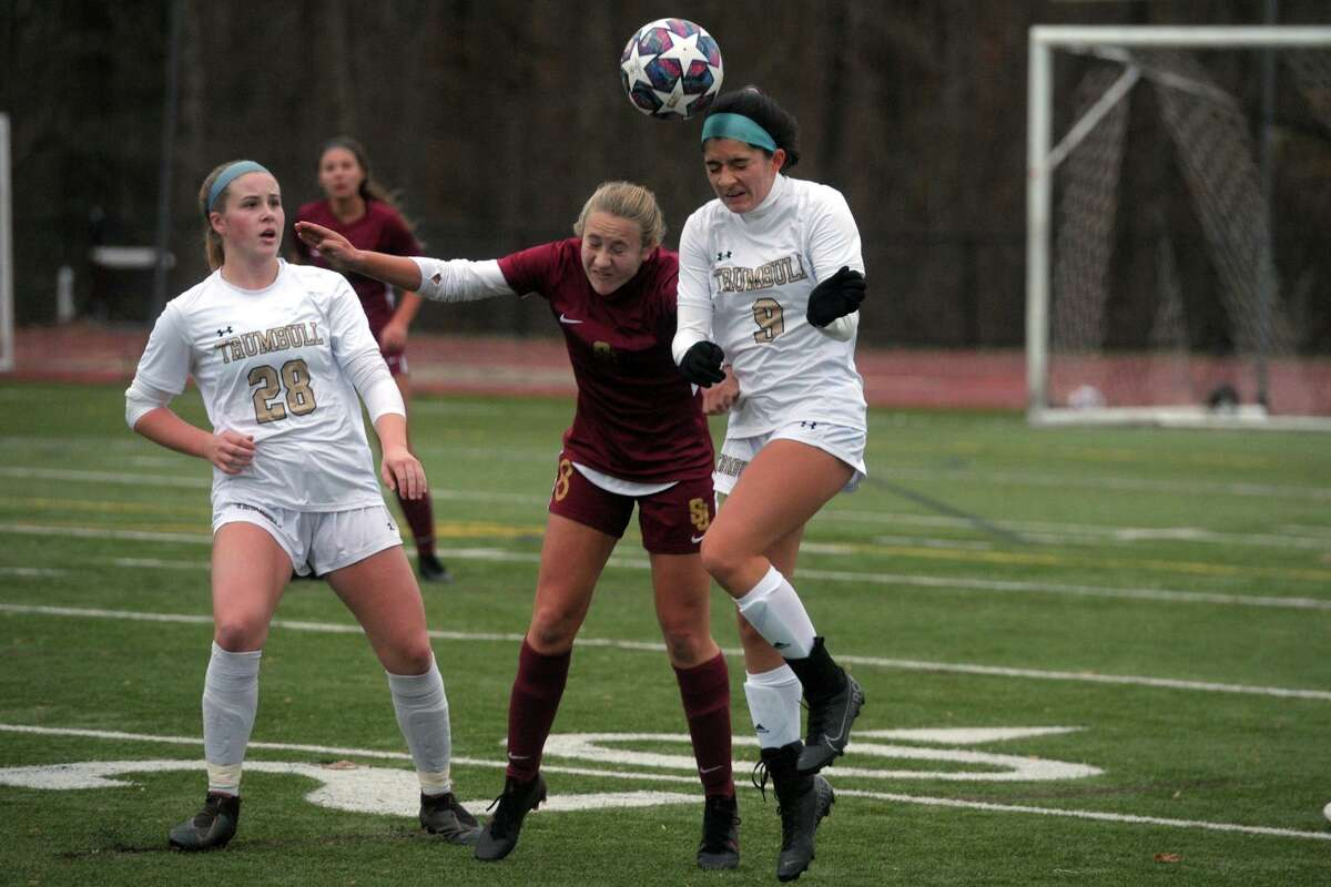 Trumbull's Korrie Munoz, right, heads the ball in front of St. Joseph's Mary Lundregan during high school soccer action at St. Joseph High School, in Trumbull, Conn. Nov. 12, 2020.