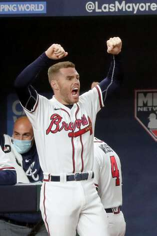 Atlanta Braves first baseman Freddie Freeman reacts in the dugout after Dansby Swanson, not pictured, hit a two-run double against the Los Angeles Dodgers during the sixth inning in Game 4 of the National League Championship Series at Globe Life Field in Arlington, Texas, on Thursday, Oct. 15, 2020. The Braves won, 10-2, for a 3-1 series lead. (Curtis Compton/Atlanta Journal-Constitution/TNS) Photo: Curtis Compton, TNS