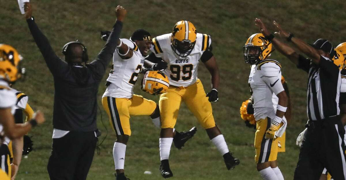 Fort Bend Marshall's Jaylon Williams (24) and Laurence Tillman (99) celebrate Williams fumble return for a touchdown against Willowridge during an 11-5A matchup at Hall Stadium Thursday, Nov. 12, 2020 in Missouri City.