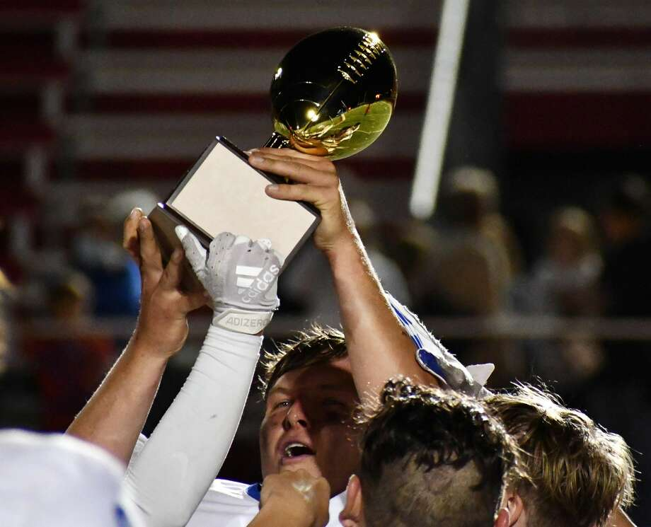 Senior Jack Allcorn lifts the gold ball trophy high in the air after Olton's 35-33 victory over New Deal in their Class 2A Division I bi-district football playoff game on Nov. 12, 2020 in Lobo Stadium in Levelland. Photo: Nathan Giese/Planview Herald