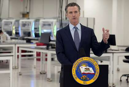 FILE - In this Oct. 30, 2020, file photo, California Gov. Gavin Newsom speaks at a COVID-19 testing facility in Valencia, Calif. Newsom eased the sentences or criminal history of nearly three dozen current or former felons, Tuesday, Nov. 10, 2020, including 10 pardons intended to aid immigrants who face the possibility of deportation. (AP Photo/Marcio Jose Sanchez, Pool, File)