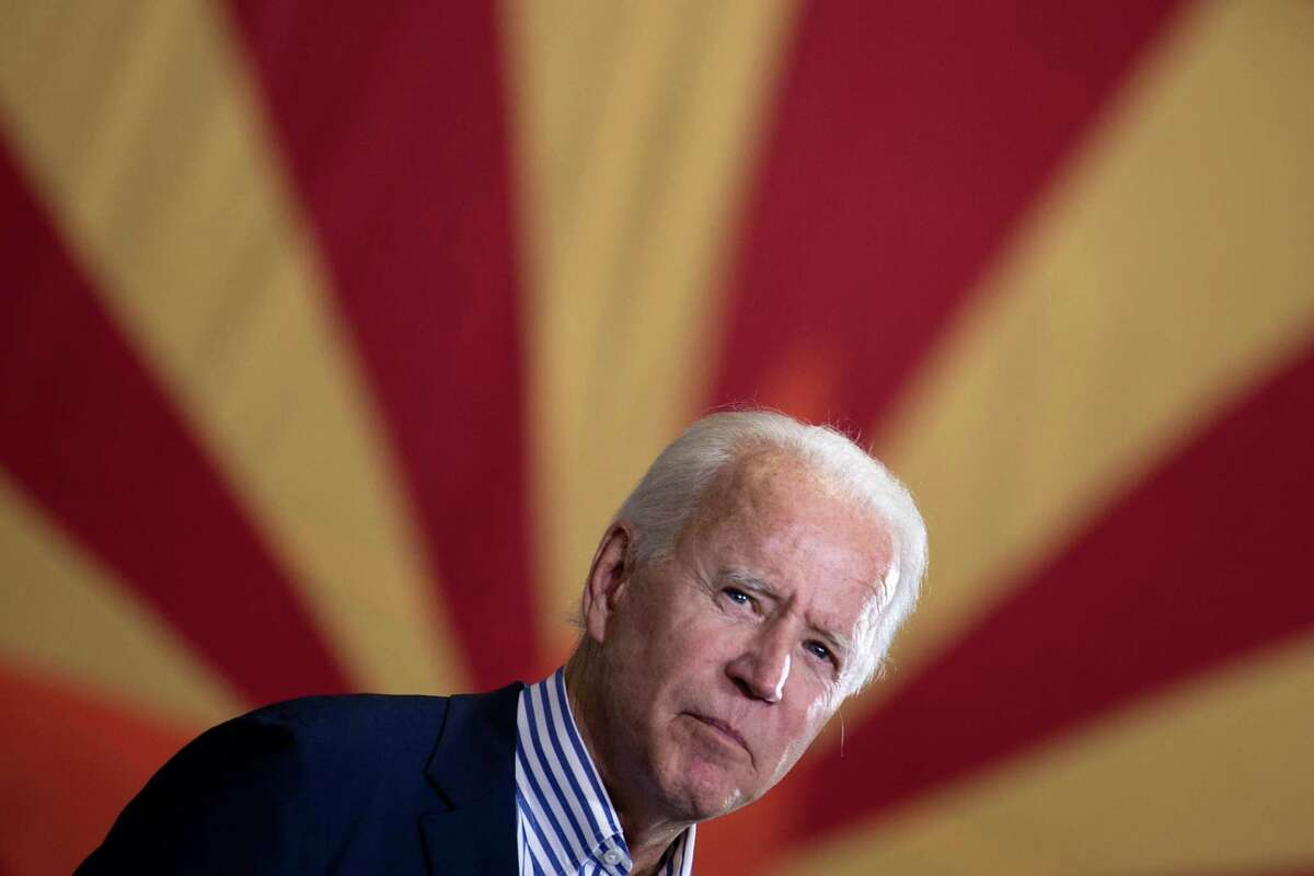 Joe Biden pauses while speaking to supporters in front of an Arizona state flag, at the United Brotherhood of Carpenters and Joiners of America's training center in Phoenix, Arizona, in October.