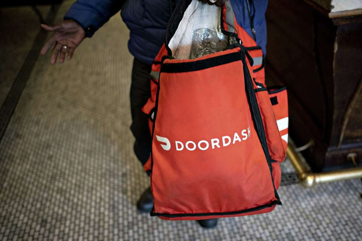 A DoorDash delivery person holds an insulated bag at Chef Geoff's restaurant in Washington on March 26, 2020.