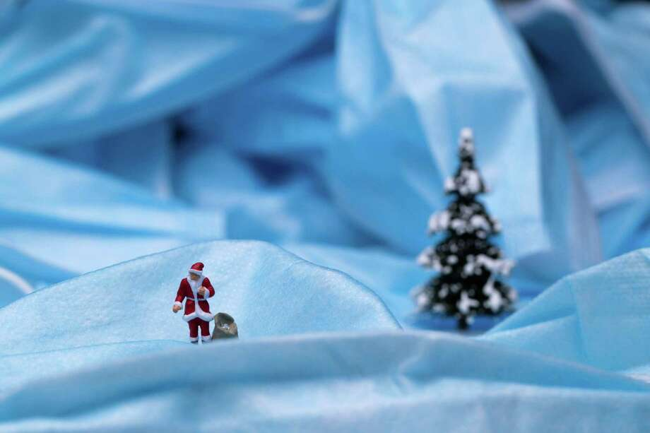 This picture taken on November 8, 2020 shows a Santa Claus figurine photographed among surgical masks in Paris, as France is on a second lockdown aimed at containing the spread of Covid-19 pandemic caused by the novel coronavirus . (Photo by JOEL SAGET / AFP) (Photo by JOEL SAGET/AFP via Getty Images) Photo: Joel Saget / AFP Via Getty Images / AFP or licensors