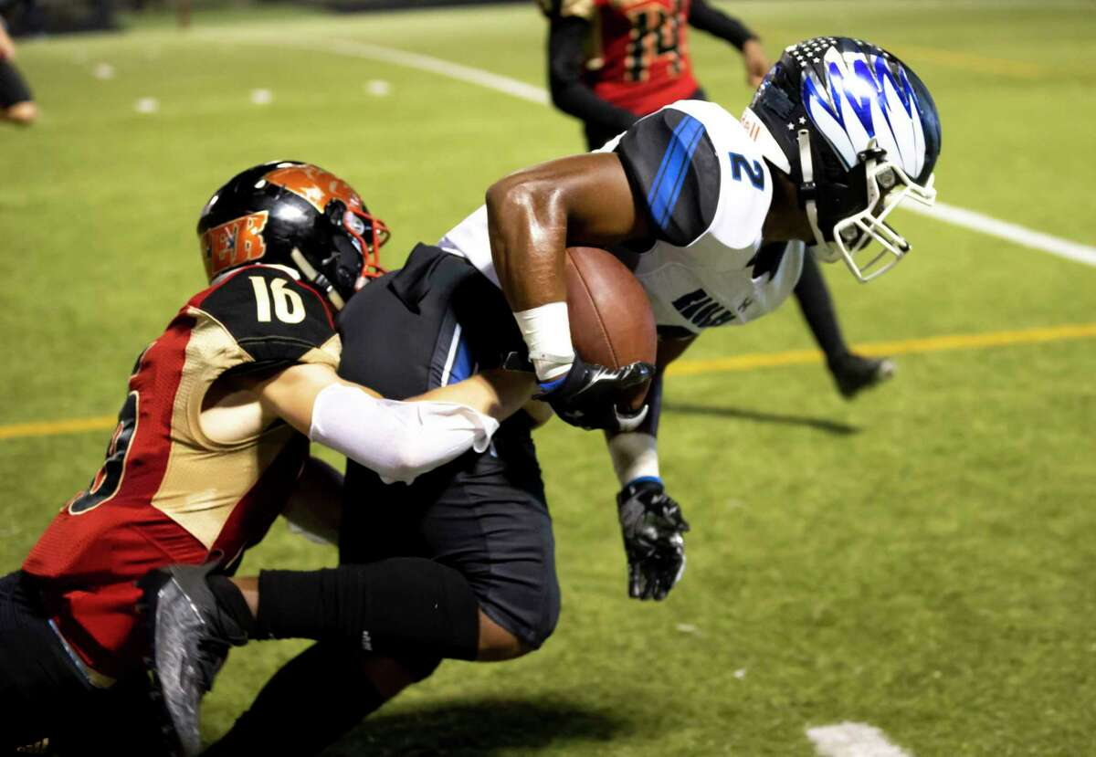 New Caney wide receiver Billy Williams Jr. (2) is pushed toward out of bounds by Caney Creek defensive back Rowdy Sebastian (16) during the second quarter of a District 8-5A (Div. I) football game at Moorhead Stadium in Conroe.