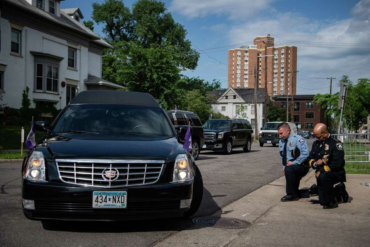 Minneapolis Police Chief Medaria Arradondo, right, kneels as the hearse carrying George Floyd's body arrives at North Central University for a June 4 funeral.