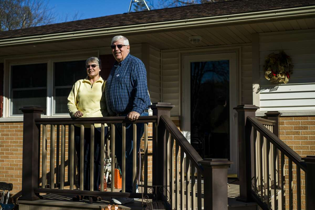 Joyce and Steve Saxton pose for a portrait on the front porch of their home Tuesday, Nov. 3, 2020 on St. Mary's Drive on Midland. (Katy Kildee/kkildee@mdn.net)